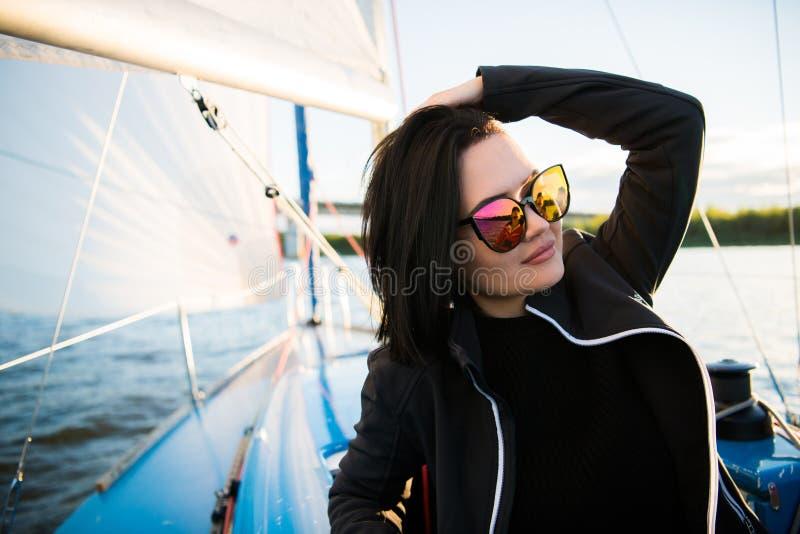 美丽的年轻女人坐游艇碗和姿势 她佩带sunglusses用手和微笑 模型在船上航行 库存照片
