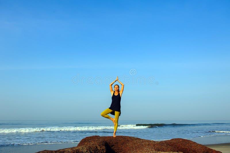 美丽的年轻女人实践的瑜伽和伸展运动在夏天海洋海滩 免版税库存图片