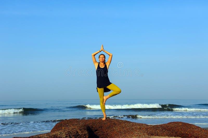 美丽的年轻女人实践的瑜伽和伸展运动在夏天海洋海滩 免版税库存照片