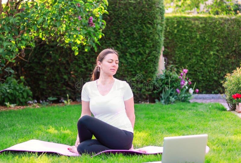 美丽的年轻女人实践的瑜伽在户外跟随网上讲解或教练员的指南庭院里在膝上型计算机 库存照片