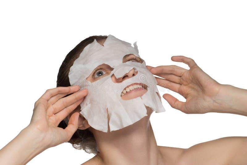 美丽的年轻女人应用在一张面孔的一个化妆面具在白色背景 免版税图库摄影