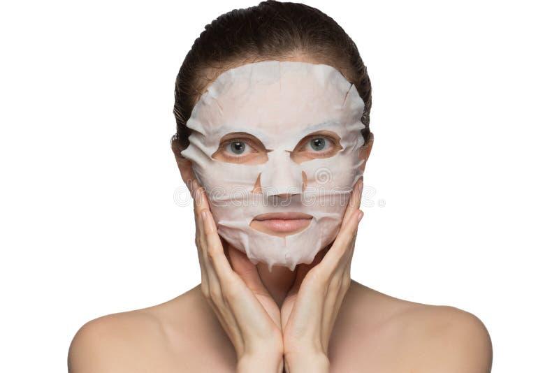 美丽的年轻女人应用在一张面孔的一个化妆面具在白色背景 库存图片