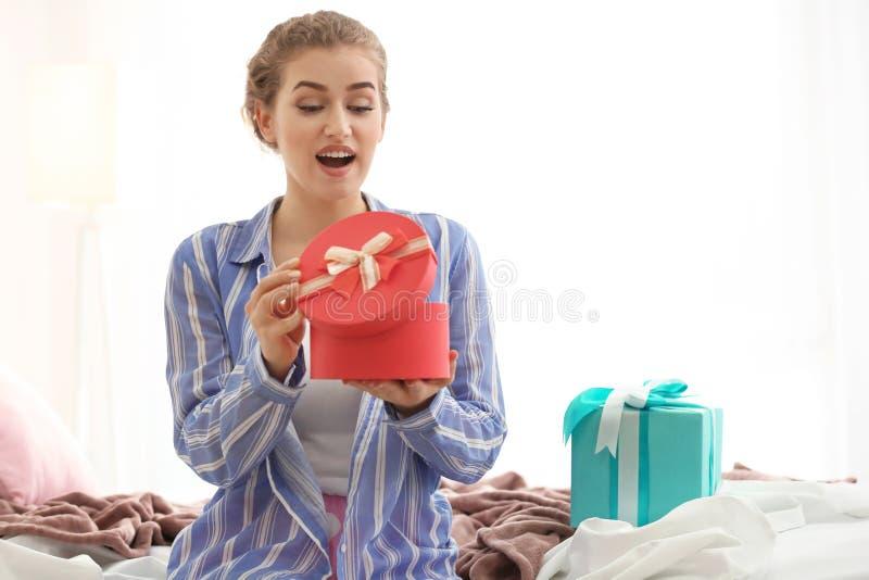美丽的年轻女人开头礼物盒在家 免版税库存图片