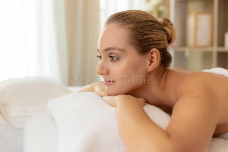 美丽的年轻女人得到放松在温泉沙龙 按摩的迷人的美女等待的按摩治疗师在美丽 库存图片
