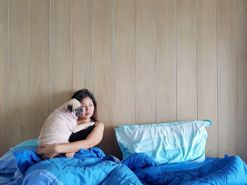美丽的年轻女人或女孩一起拥抱并且拥抱她的最好的朋友哈巴狗小狗,睡眠休息在行家的毯子下 免版税库存图片