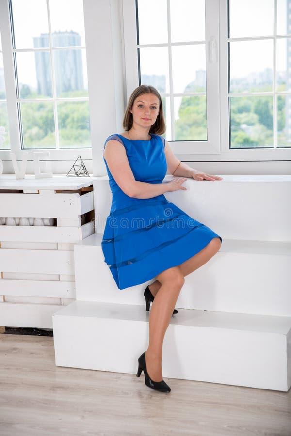 美丽的年轻女人画象在演播室 白种人女孩坐楼梯在窗口附近 夫人是愉快和微笑 妇女厕所 库存图片