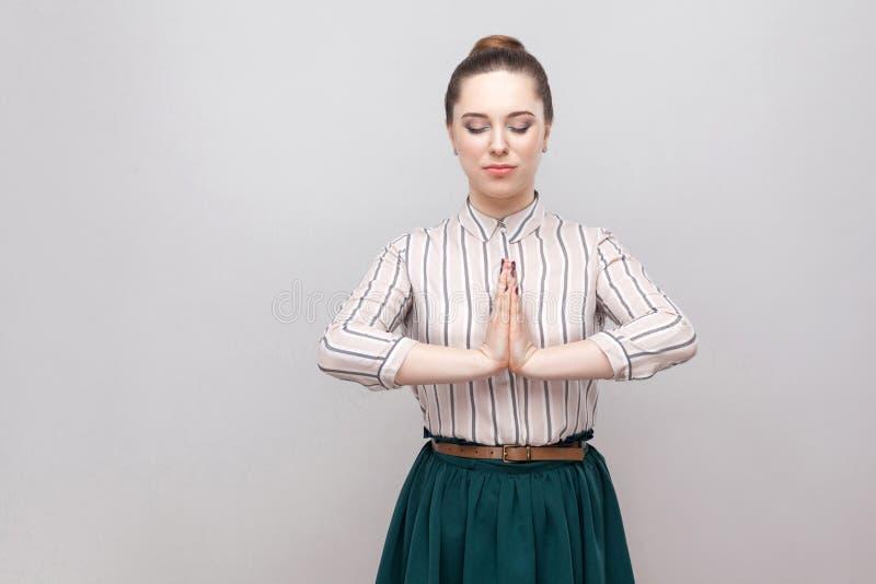 美丽的年轻女人画象安静镶边衬衣、绿色裙子有构成的和收集的禁令发型的,站立与闭合 图库摄影