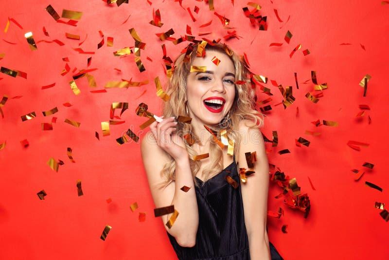 美丽的年轻女人画象有党口哨和落五彩纸屑的在颜色背景 免版税库存图片