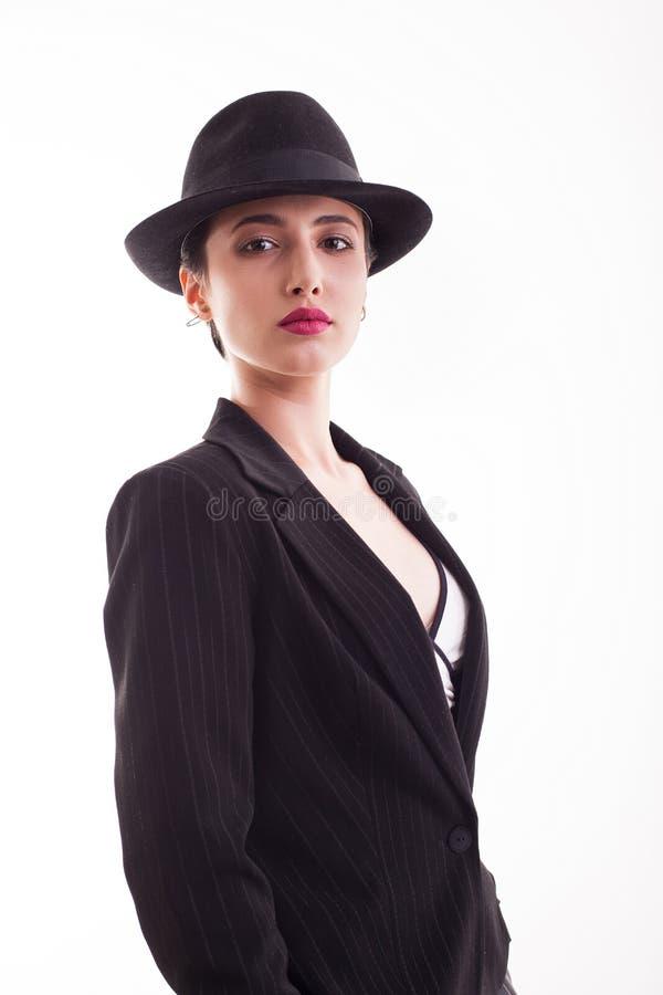 美丽的年轻女人画象有戴在白色背景的短发的时髦的黑帽会议在演播室 免版税库存图片