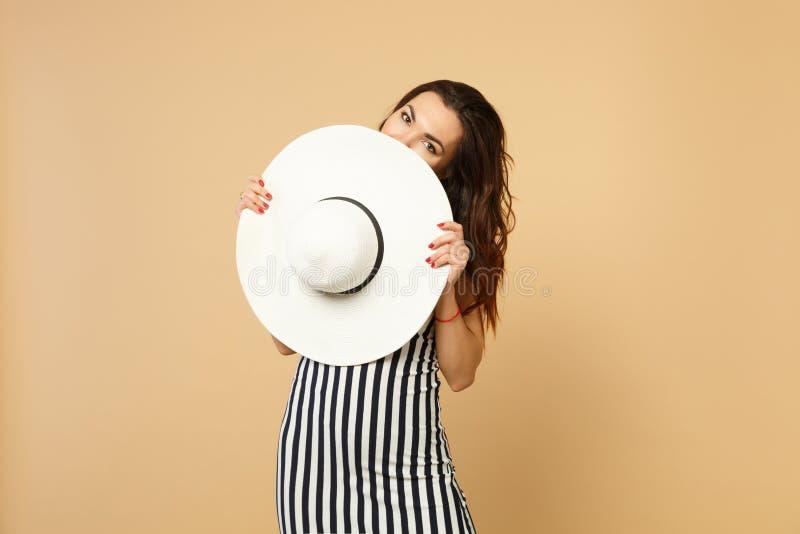 美丽的年轻女人画象黑白镶边礼服覆盖物面孔的与在淡色灰棕色隔绝的帽子 免版税库存图片