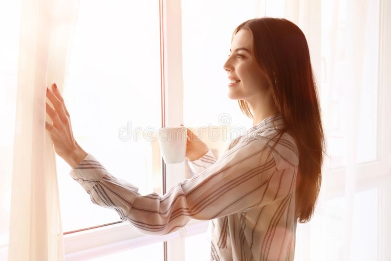 美丽的年轻女人的早晨有咖啡的在窗口附近的 库存图片