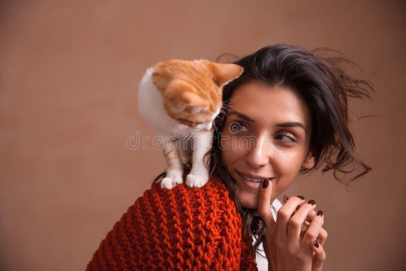 美丽的年轻女人的画象有一只小猫的在肩膀 爱的动物的概念,保重和获得乐趣与 图库摄影