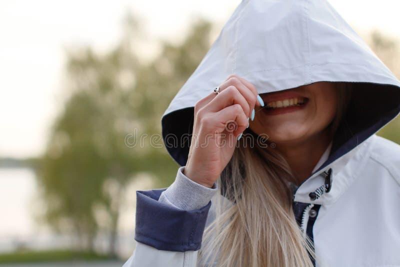 美丽的年轻女人盖她的面孔在敞篷和愉快地微笑下 一部分的金发碧眼的女人的女性面孔 库存图片