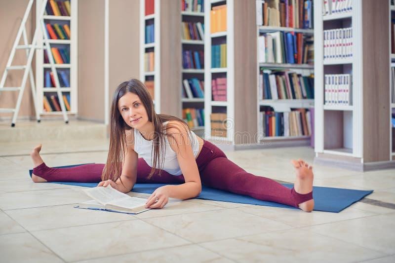 美丽的年轻女人看书和实践瑜伽asana Samakonasana平角姿势在图书馆里 库存照片