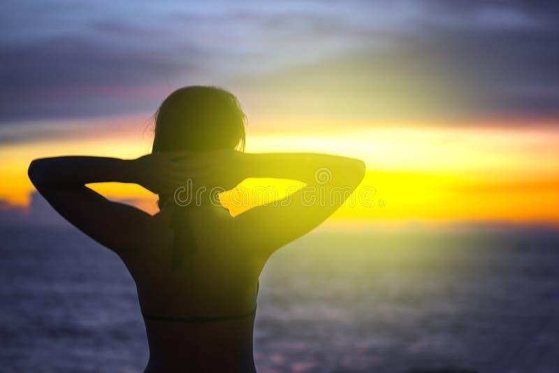 美丽的年轻女人看以欢欣海和天空在日落 剪影,特写镜头,明亮的颜色 r 免版税库存图片