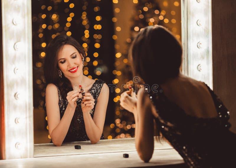 美丽的年轻女人穿在镜子前面的豪华礼服有红色口红的 免版税库存照片