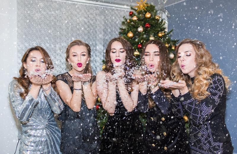 美丽的年轻女人获得乐趣在圣诞派对、吹的去五彩纸屑和雪,送亲吻 免版税库存照片