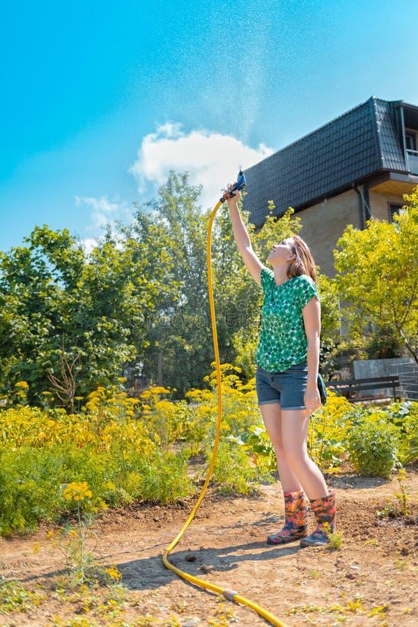 美丽的年轻女人获得乐趣在有飞溅雨的水管的夏天庭院 夏天喜悦和庭院工作的概念 免版税库存照片