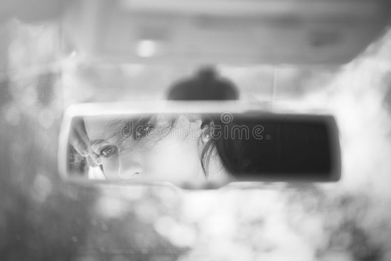 美丽的年轻女人面孔的黑白艺术图片在汽车后视镜的 库存图片