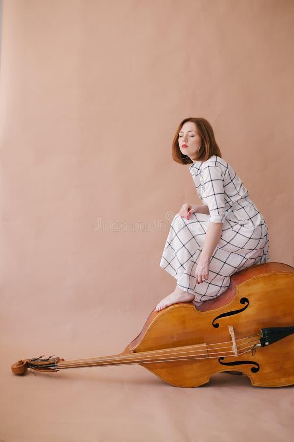 美丽的年轻女人音乐家坐在米黄背景的葡萄酒低音提琴 库存照片