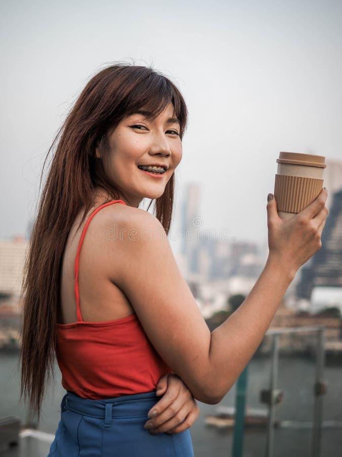 美丽的年轻女人饮用咖啡有城市视图在背景,生活方式现代 库存照片