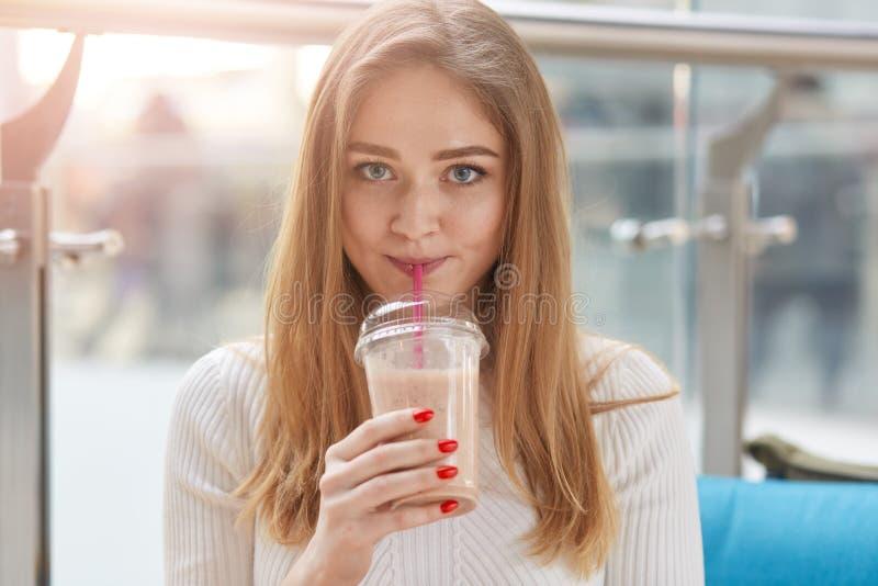 美丽的年轻女人饮用奶鸡尾酒室内射击,看直接地照相机,有新鲜的baverage的举行杯子在她的手上 库存图片