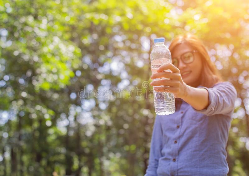 美丽的年轻女人饮用水在完成跑步以后的早晨 库存图片