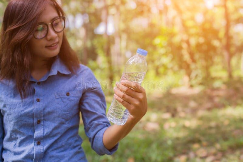 美丽的年轻女人饮用水在完成跑步以后的早晨 免版税图库摄影