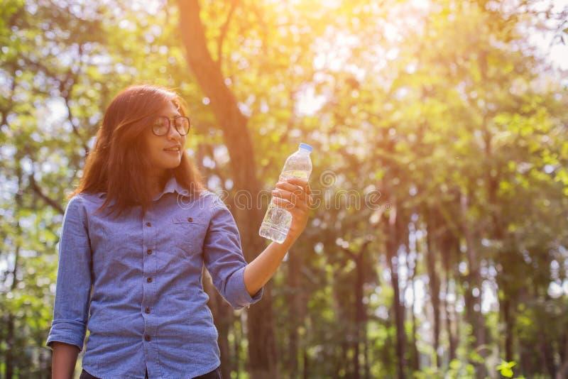 美丽的年轻女人饮用水在完成跑步以后的早晨 库存照片