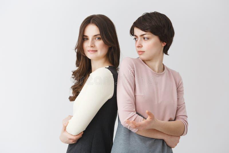美丽的年轻女同性恋的学生女孩画象有摆在与短发白种人女朋友的长的头发的 免版税图库摄影