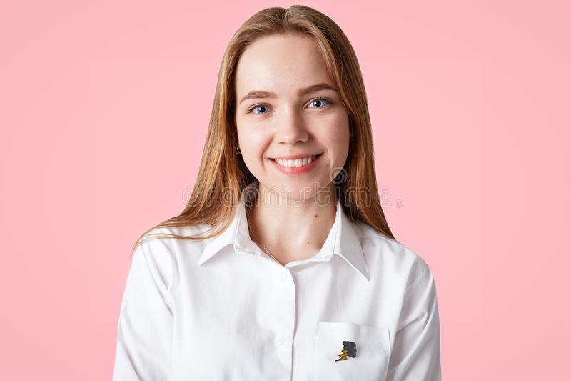 美丽的年轻女学生有健康皮肤,蓝眼睛,并且正面微笑,穿白色典雅的衬衣,摆在反对桃红色backg 库存图片
