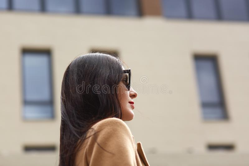 美丽的年轻女实业家画象室外在被弄脏的街道背景 典雅的深色的女性档案,佩带米黄 库存照片