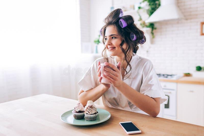 美丽的年轻女性主妇在厨房里 举行杯子和神色支持 单独微笑 薄煎饼和电话在桌上 库存照片