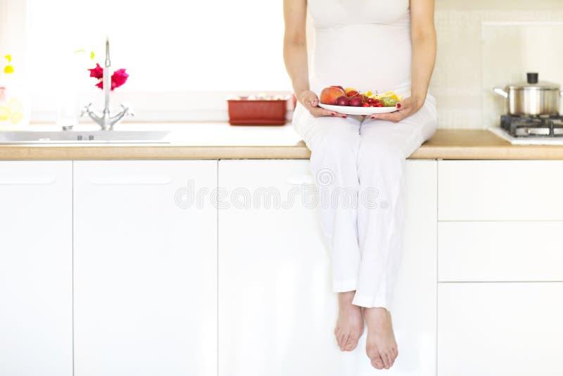 美丽的年轻孕妇用果子在厨房里 免版税库存照片