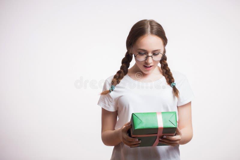 美丽的年轻学生女孩接受了一件期待已久的礼物,充满看在白色背景的惊奇和喜悦绿色箱子 库存照片