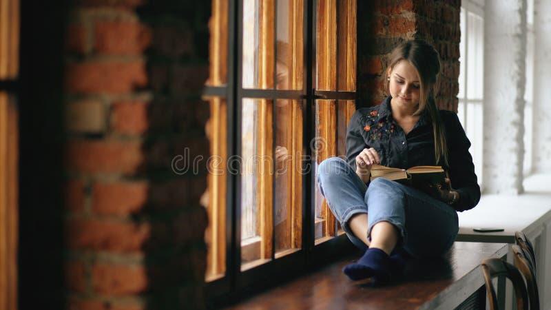 美丽的年轻学生女孩阅读书坐窗台在大学教室户内 免版税库存照片