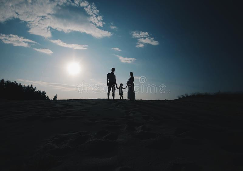 美丽的年轻家庭剪影画象在期望的新出生 男人和妇女身分面对面与他们 库存图片