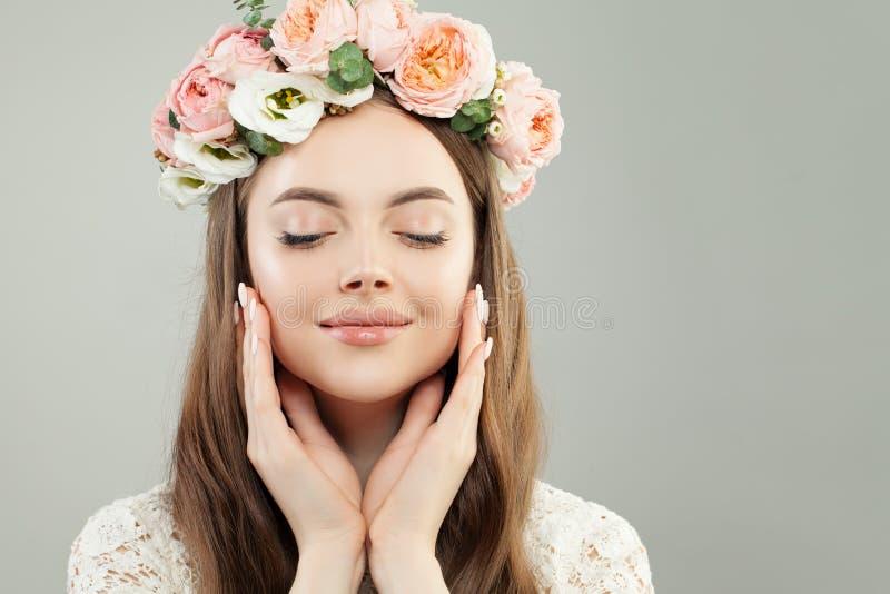 美丽的年轻式样妇女画象有健康清楚的皮肤、自然构成和春天花的,女性面孔特写镜头 库存照片