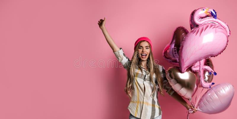 美丽的年轻快乐的女孩拿着一束在桃红色淡色背景的桃红色气球 免版税库存图片