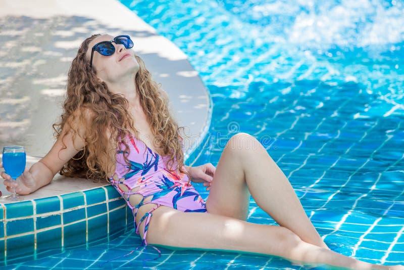 美丽的年轻性感的有喝在游泳场的太阳镜的妇女佩带的比基尼泳装鸡尾酒 摆在的泳装的俏丽的女孩和 库存图片