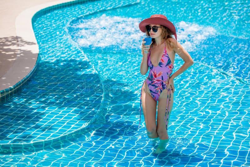 美丽的年轻性感的有太阳镜和红色帽子饮用的鸡尾酒的妇女佩带的比基尼泳装在游泳场 泳装的俏丽的女孩 免版税图库摄影