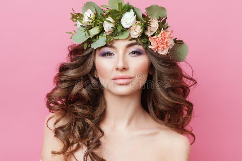 美丽的年轻性肉欲的妇女画象有完善的皮肤的在桃红色背景的头组成卷发和花 Wrea 免版税图库摄影