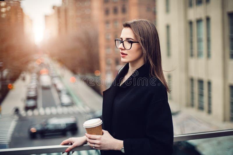 美丽的年轻成人女商人饮用的咖啡在早晨时间的城市 免版税库存图片