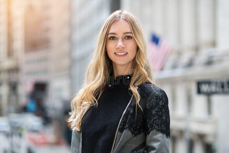 美丽的年轻成人微笑的女实业家画象在纽约华尔街 库存图片