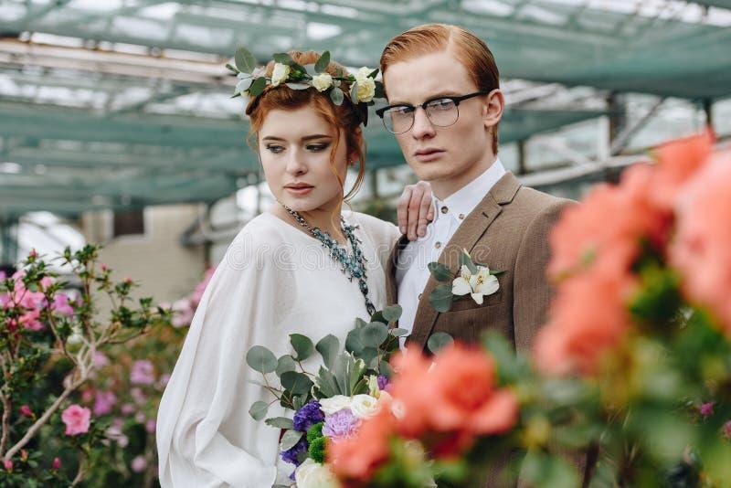 美丽的年轻新郎和新娘有一起站立在植物的婚礼花束的 免版税图库摄影