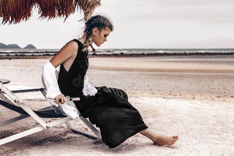 美丽的年轻时髦的在海滩的妇女坐的轻便折叠躺椅 库存照片