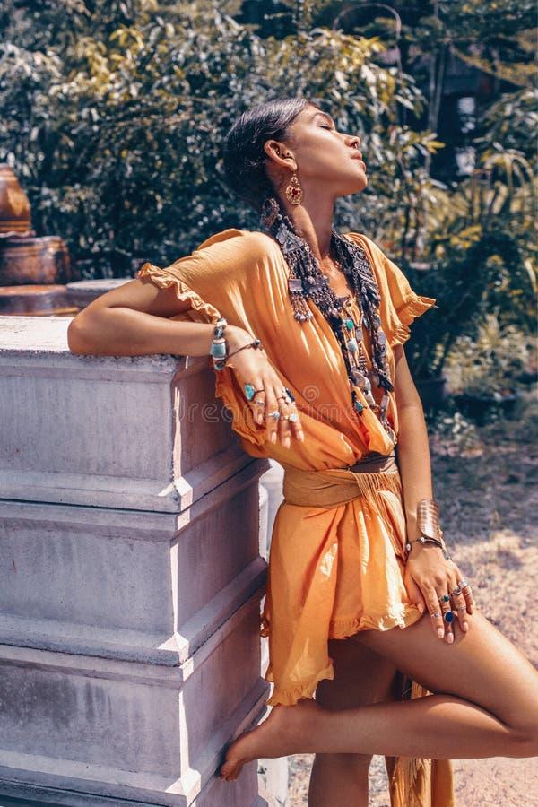 美丽的年轻时髦的女人与组成和摆在时髦的boho的辅助部件在自然热带背景 图库摄影