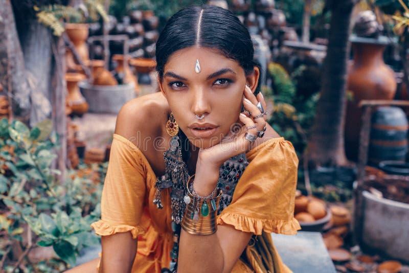 美丽的年轻时髦的女人与组成和摆在时髦的boho的辅助部件在自然热带背景 库存照片