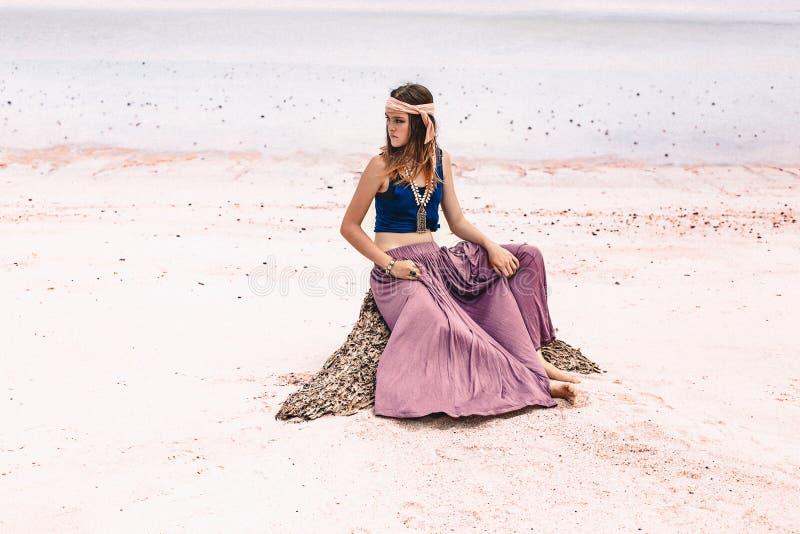 美丽的年轻时髦的妇女坐在海滩的沙子 免版税库存图片