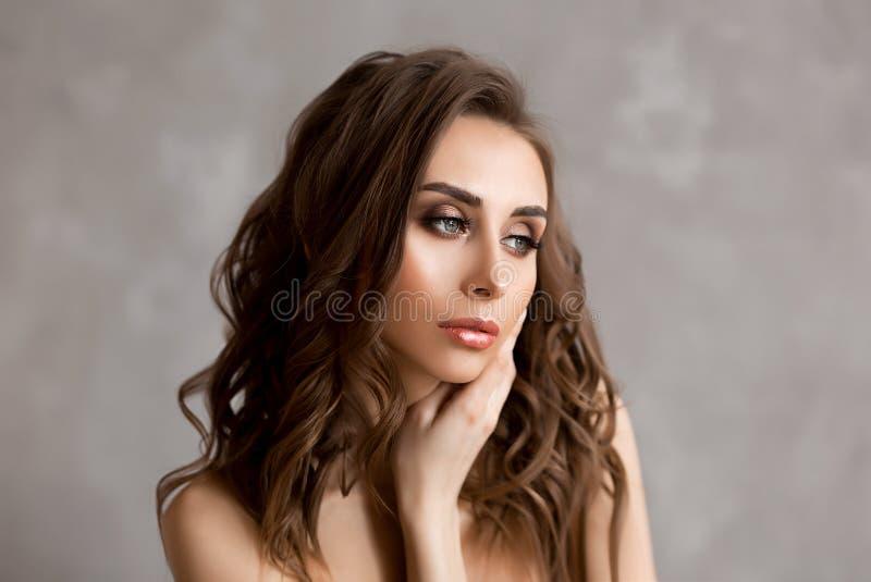 美丽的年轻欧洲长期妇女eith黑暗的卷发和蓝眼睛,俏丽和性感的白种人年轻女人画象  库存图片